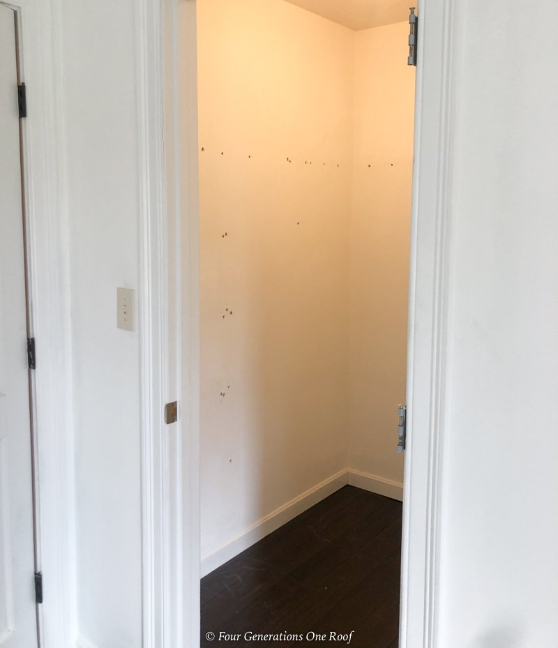 empty walk in closet with holes in wall from wire shelving