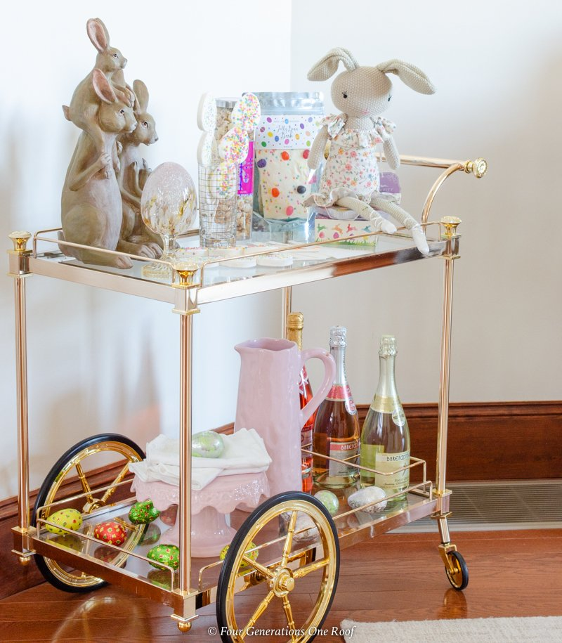 gold and glass bar cart filled with Easter decorations and Easter candy