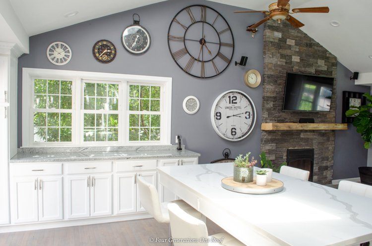 split level house with kitchen wall removed + white kitchen cabinets with 3 windows + rustic beam mantel