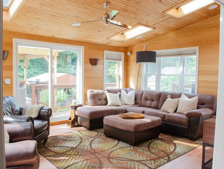 sunroom with vaulted ceiling, wood plank walls and wood ceiling, brown suede sectional, patio doors
