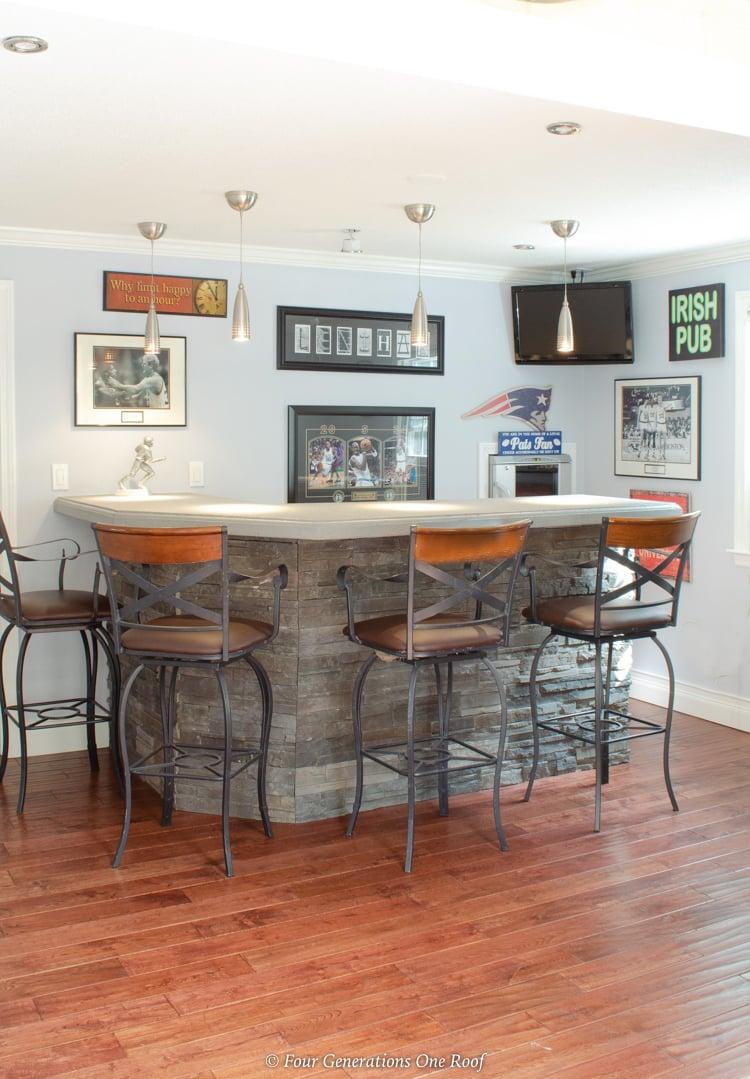 stone sports bar with rod iron leather bar stools, hardwood flooring