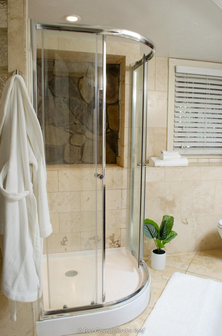 light brown marble tile shower with glass door