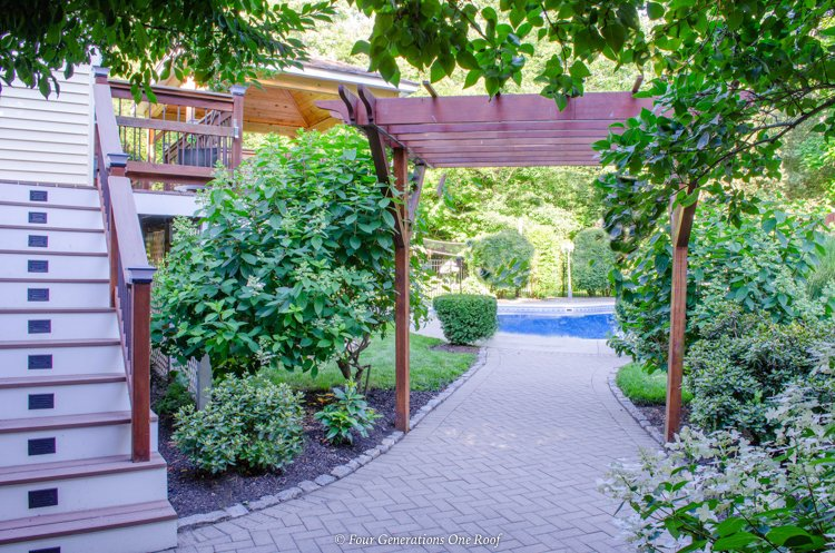 paver walkway leading to inground pool with arbor covered greenery