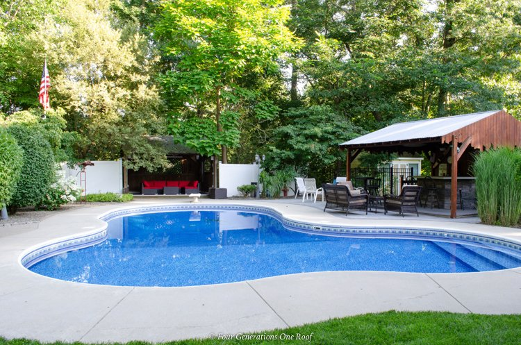 inground pool with patio and pool cabana with metal roof