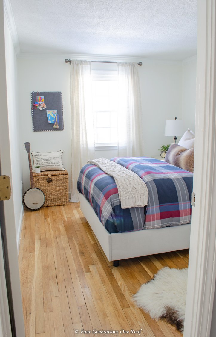 boys white bedroom with plaid bedding and world map on wall