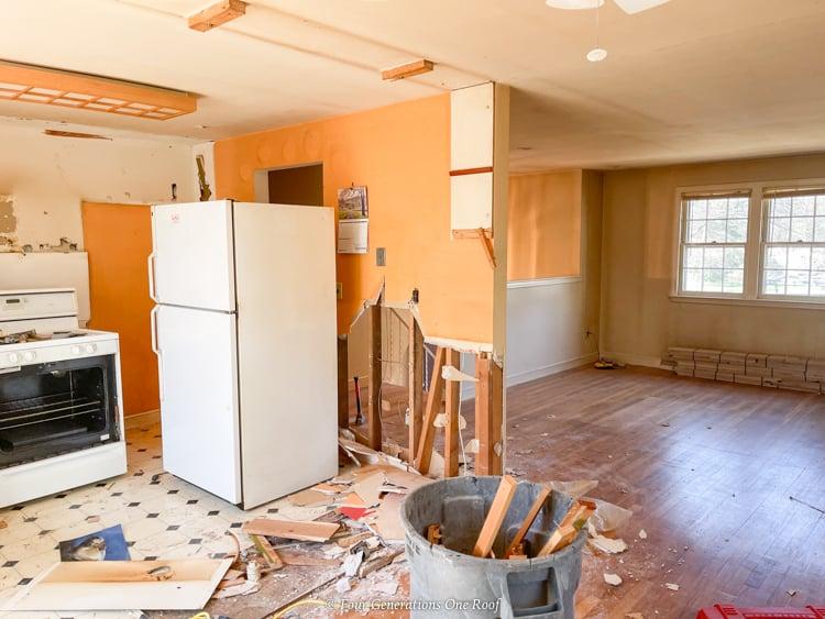 1970s split level kitchen with parkay floor, load bearing wall demo, hardwood floor, old white refrigerator