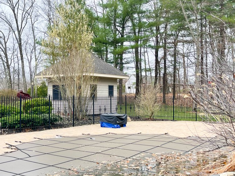 small pool house with black iron fence, elephant pool cover on pool, paver patio