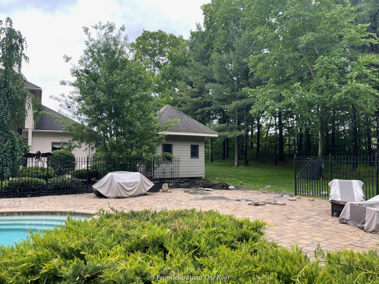 small pool house with black iron fence and pool