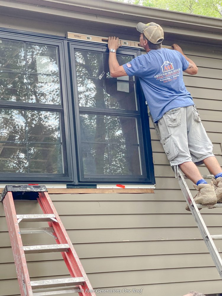 checking black window is level on brown siding
