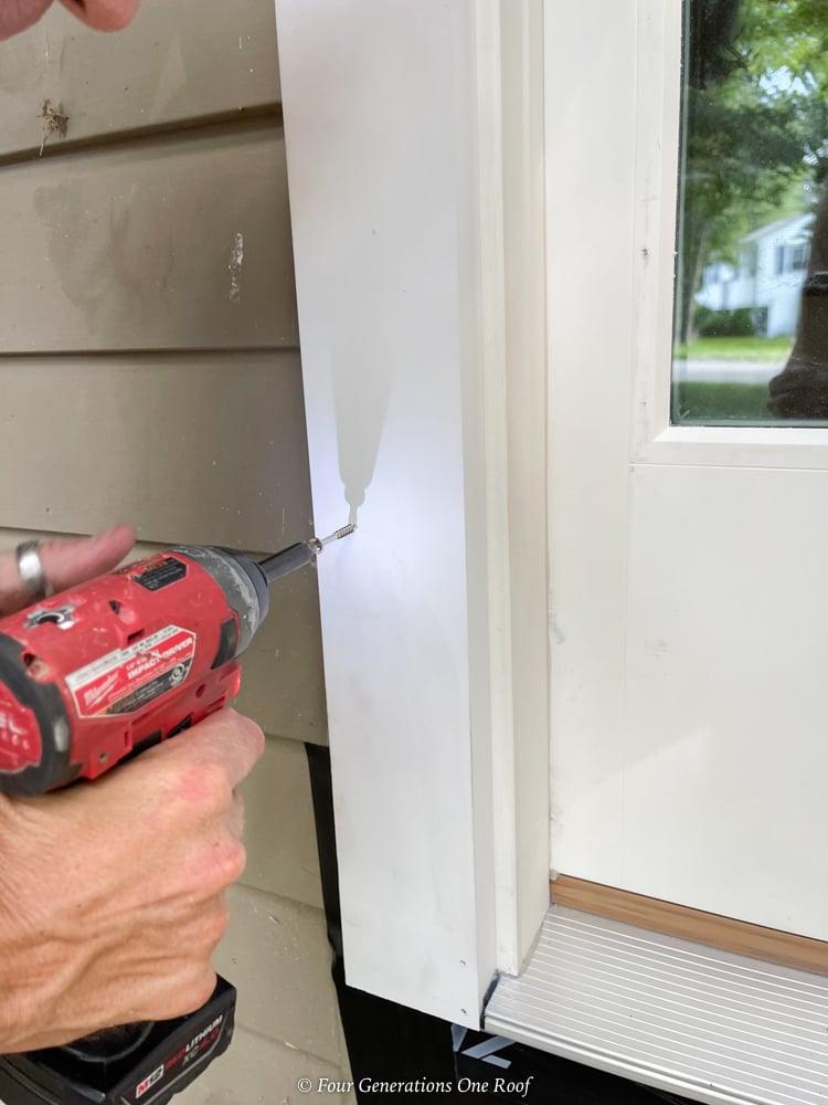 screwing a prehung front door to the door frame