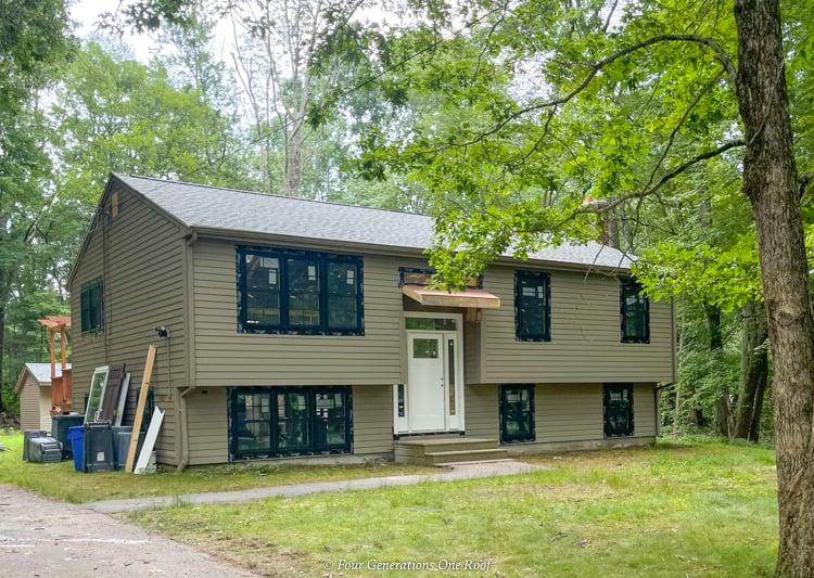 brown split level house black windows craftsman front door with sidelights