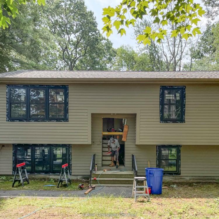 brown split level home black windows front door opening door replacement